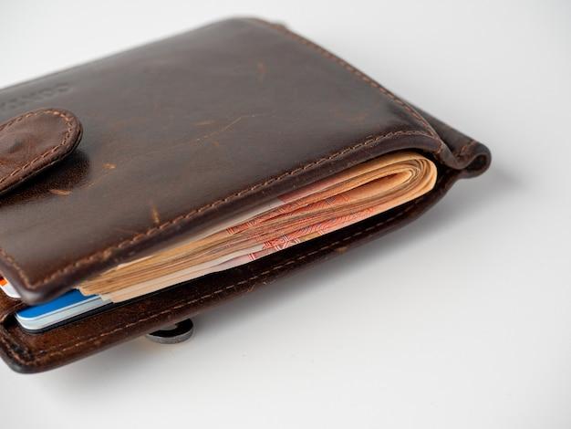 Gros plan sur un portefeuille en cuir marron plein de billets de banque sur fond blanc. le concept de richesse, de profit, de richesse