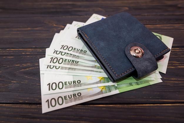 Gros plan sur un portefeuille d'homme en cuir et cent billets en euros sur un fond en bois. concept de richesse, de succès et de finance