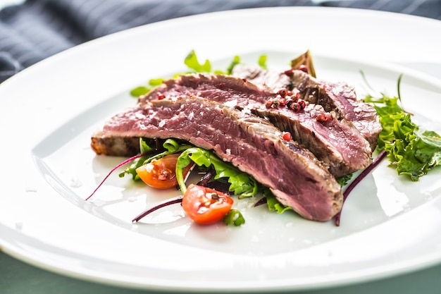 Gros plan sur une portion de bifteck de flanc juteux de salade de légumes sel poivre et romarin sur plaque blanche.