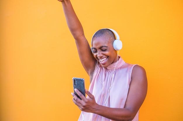 Gros plan et portrait d'une belle femme afro-américaine souriante et s'amusant à danser tout en écoutant de la musique avec les écouteurs de son téléphone - profitant d'un mode de vie technologique