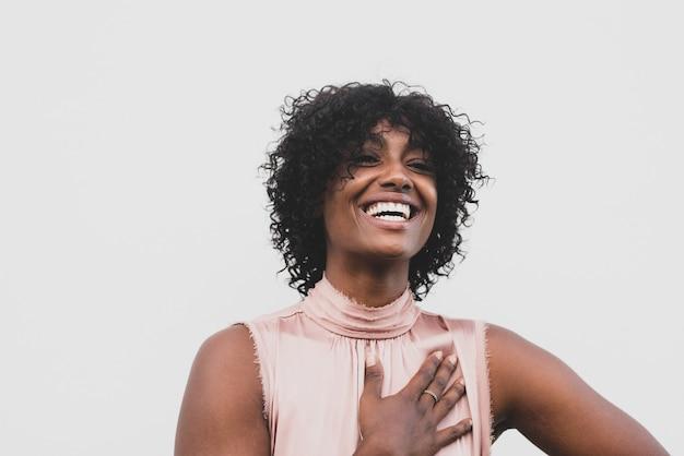 Gros plan et portrait d'une belle femme afro souriante et riant avec un fond blanc - grand sourire de jeune femme afro-américaine