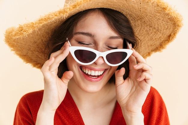 Gros plan portrait de belle femme brune vacances portant un chapeau de paille et des lunettes de soleil à la mode souriant isolé