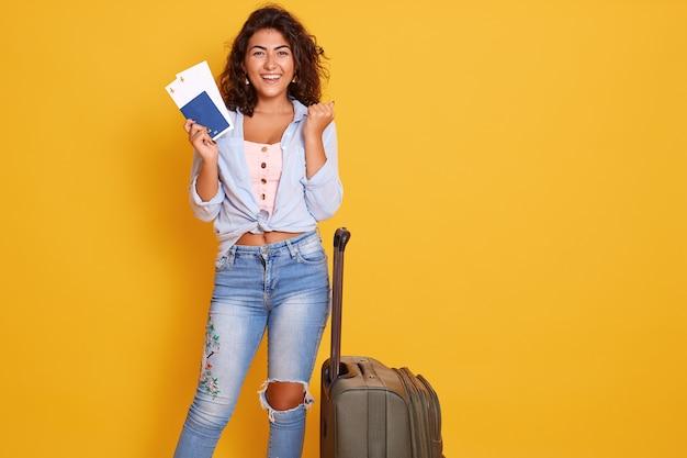 Gros plan le portrait de la belle jeune femme brune portant un jean élégant et une chemise bleue