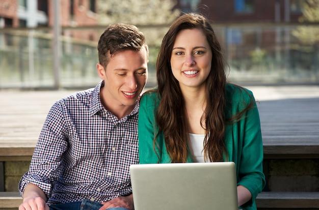 Gros plan portrait de deux étudiants travaillant sur ordinateur portable à l'extérieur