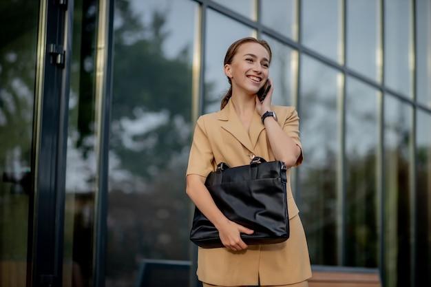 Gros plan portrait d'une femme d'affaires debout à l'extérieur de l'immeuble de bureaux et parlant au téléphone portable.