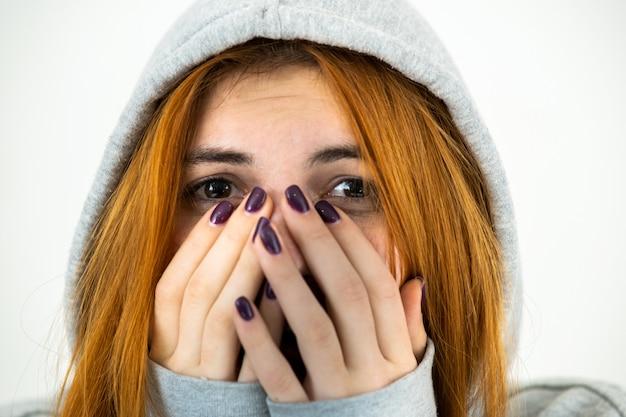 Gros plan le portrait d'une femme jeune rousse effrayée portant un pull à capuche chaud.
