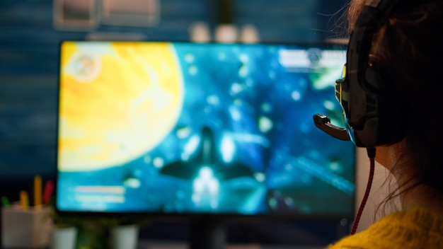Gros plan sur le portrait de femme d'un joueur professionnel jouant à un jeu vidéo informatique parlant dans un casque avec des coéquipiers en championnat. équipe d'esport diversifiée de joueurs professionnels jouant à l'ordinateur