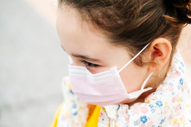Un gros plan le portrait d'une fille avec un masque rose et un manteau de fleurs