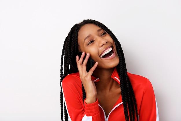Gros plan, portrait, de, gaie, jeune femme, à, cheveux tressés, parler au téléphone portable et rire