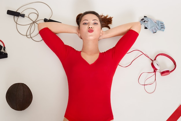 Gros plan, portrait, de, heureux, caucasien, femme, pose, blanc, surface, entouré, différent, équipement sport: expander, fitness, gants
