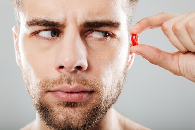 Gros plan le portrait d'un homme barbu tenant une capsule rouge