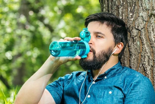 Gros plan le portrait d'un homme buvant de l'eau provenant d'une bouteille à l'extérieur