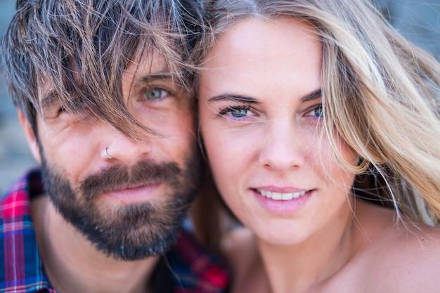 Gros plan et portrait d'un homme et d'une femme beaux et beaux ensemble avec leurs visages l'un près de l'autre en regardant la caméra en souriant - femme blonde aux yeux bleus et bel homme aux yeux verts