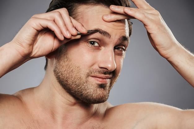 Gros plan le portrait d'un homme torse nu effrayé, arrachant les sourcils