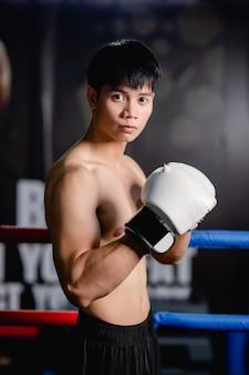 Gros plan, portrait jeune bel homme en gants de boxe blancs pose debout sur toile dans une salle de sport, cours de boxe d'entraînement pour homme en bonne santé,