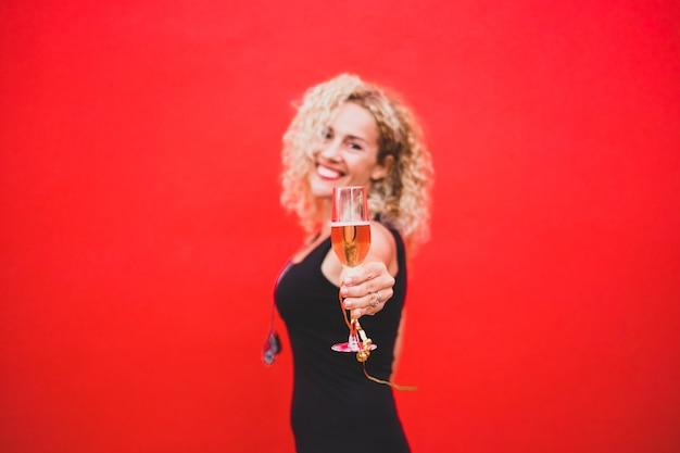 Gros plan et portrait d'une jeune et belle femme frisée souriante et tenant un verre de champagne en regardant la caméra - concept de fête du nouvel an
