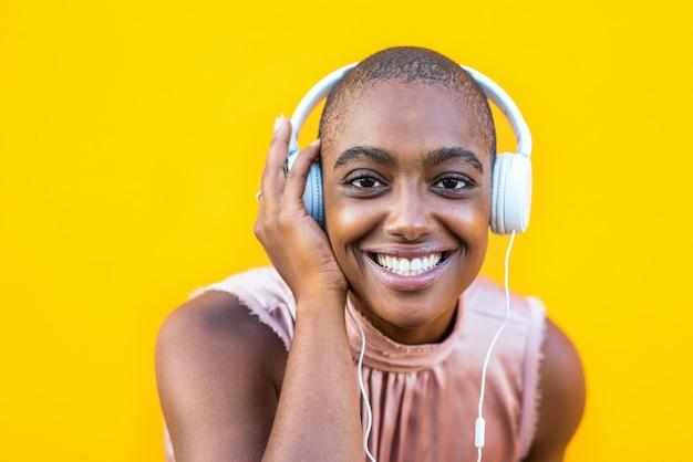 Gros plan et portrait d'une jeune femme afro-américaine regardant la caméra en souriant et en profitant de la musique avec ses écouteurs - fond jaune