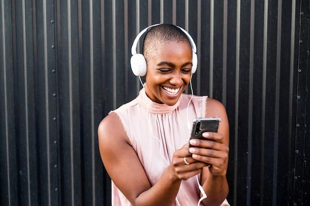 Gros plan et portrait d'une jeune femme afro-américaine utilisant son téléphone ou son portable tout en écoutant de la musique avec des écouteurs - des gens heureux s'amusant et appréciant d'entendre de la musique - mur noir en arrière-plan