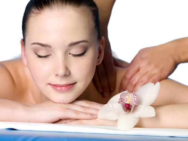 Gros plan portrait de jeune femme ayant un massage dans un salon spa - nackground blanc