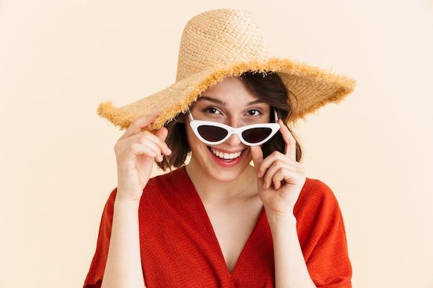 Gros plan portrait de jeune femme brune vacances portant un chapeau de paille et des lunettes de soleil à la mode souriant isolé