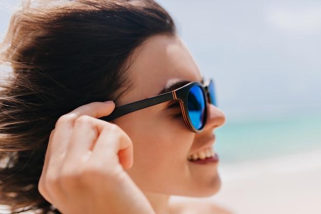 Gros plan portrait de jeune femme à lunettes de soleil posant sur la nature flou. fascinante femme caucasienne aux cheveux noirs, profitant de l'été à la station balnéaire.