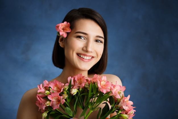 Gros plan le portrait d'une jeune femme tendre avec des fleurs roses sur un mur bleu