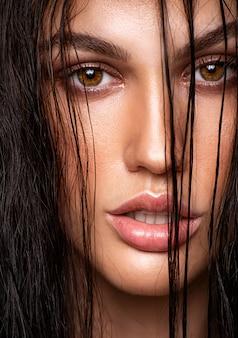 Gros plan - portrait d'une jolie brune aux cheveux mouillés