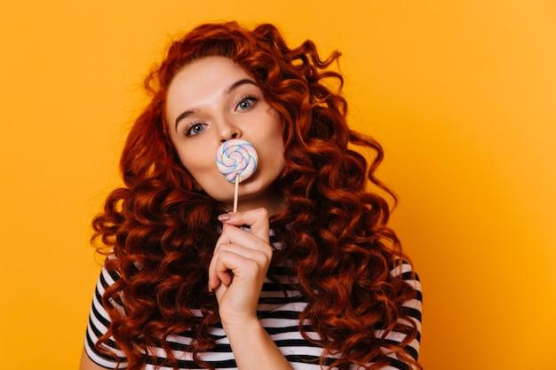 Gros plan portrait de jolie fille au gingembre aux yeux bleus posant avec grosse sucette sur l'espace orange.
