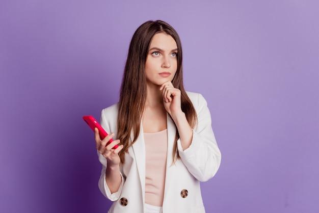 Gros plan portrait de profil de dame tenir le menton du doigt du téléphone penser porter un costume formel posant sur un mur violet