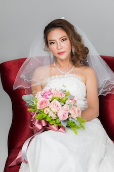 Gros plan portrait de sourire belle mariée asiatique assise sur une chaise rouge tenant un bouquet de fleurs sur fond noir gris.