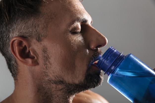 Gros plan le portrait d'un sportif torse nu mature boire de l'eau