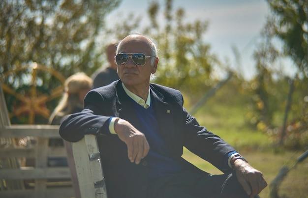 Gros plan portrait de vieil homme assis dans le jardin