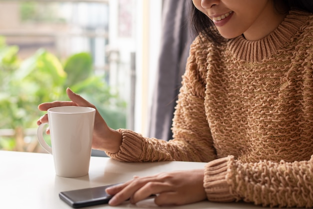 Gros plan, positif, femme, regarder, nouvelles en ligne, sur, smartphone