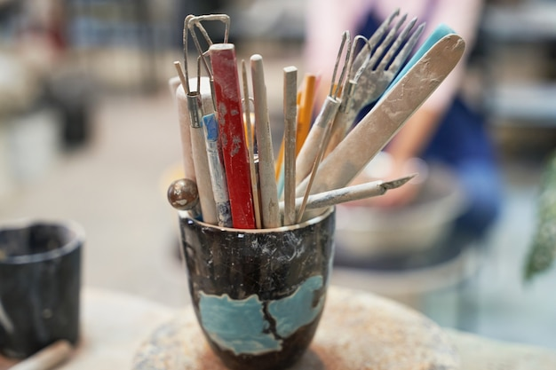 Gros plan sur un pot avec des outils, des pinceaux pour créer des céramiques d'argile faites à la main dans un atelier