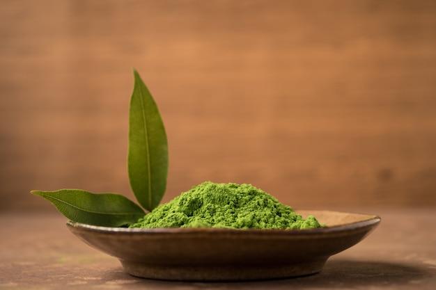 Gros plan de poudre de thé vert avec des feuilles dans un plat en céramique sur la table.