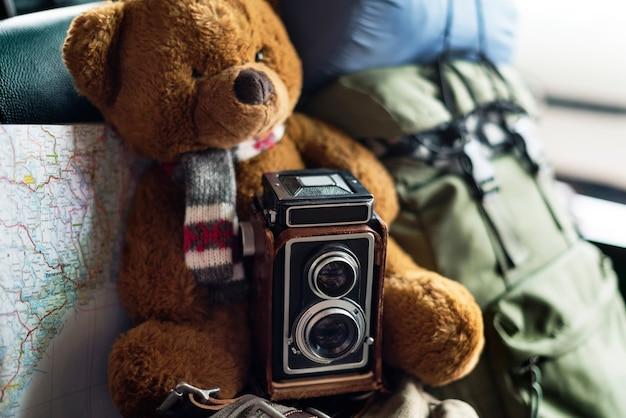 Gros plan d'une poupée ours brun avec appareil photo et carte de voyage