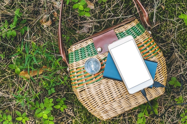 Gros plan, powerbank avec maquette de smartphone sur un panier dans la forêt. notion de voyage.