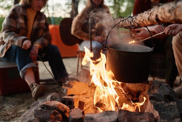 Gros plan de la préparation des aliments dans une casserole sur un feu avec des gens assis en arrière-plan