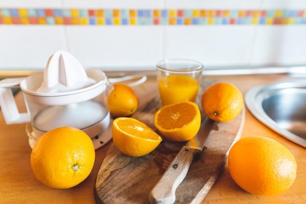 Gros plan de presse-agrumes électrique, couteau et oranges sur le comptoir de la cuisine.