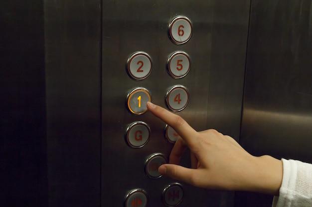 Gros plan d'une presse à main de femme d'ascenseur.