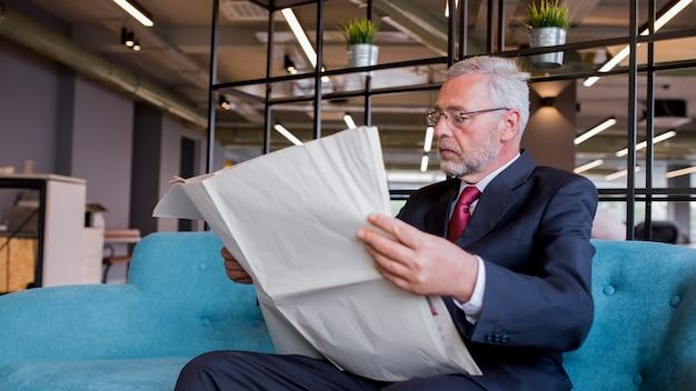 Gros plan, principal, homme affaires, s'asseoir divan, journal lecture, dans bureau