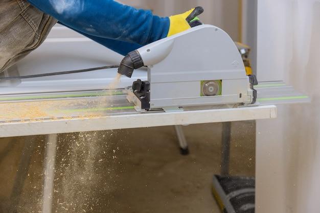 Gros plan sur le processus de coupe d'une scie circulaire à main sur des coupes de portes en bois sur une rénovation de maison.
