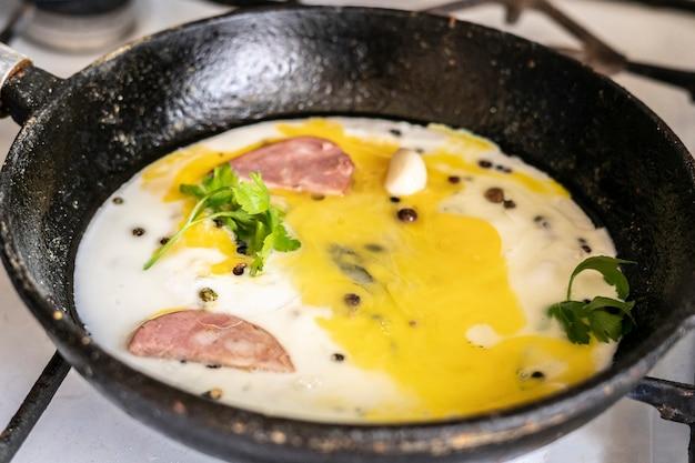 Gros plan sur le processus de cuisson des œufs brouillés dans une poêle à frire huilée chaude avec du poivre et des herbes