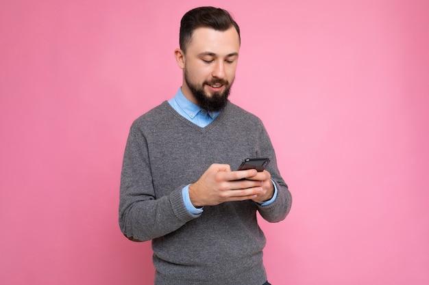 Gros plan de profil latéral photo d'un beau jeune homme positif et beau portant une tenue élégante décontractée isolée sur fond avec un espace vide tenant dans la main et utilisant un message de téléphone portable
