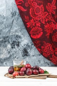 Gros plan des prunes et de l'eau de désintoxication sur une planche à découper avec un morceau de sac et un rideau rouge sur une planche de bois blanche et une surface en marbre bleu foncé. verticale