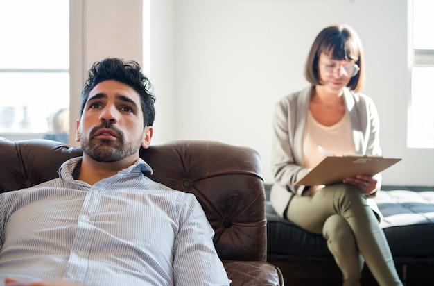 Gros plan d'un psychologue prenant des notes sur le presse-papiers pendant que son patient est allongé sur le canapé pendant la séance de thérapie