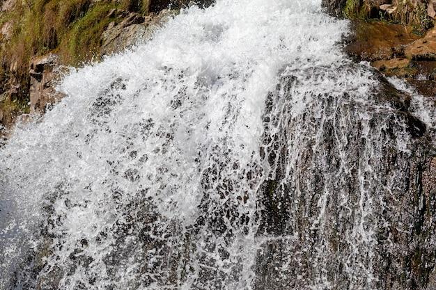 Gros plan d'une puissante cascade de haute qualité. vue latérale d'une cascade ensoleillée à l'état sauvage. un grand jet d'eau se déverse de la montagne.