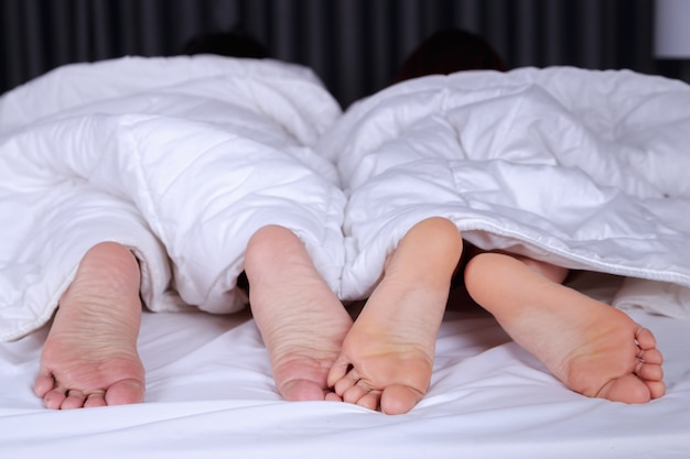 Gros plan de quatre pieds dans le lit