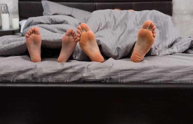 Gros plan de quatre pieds sous couverture grise dans un lit moderne et élégant