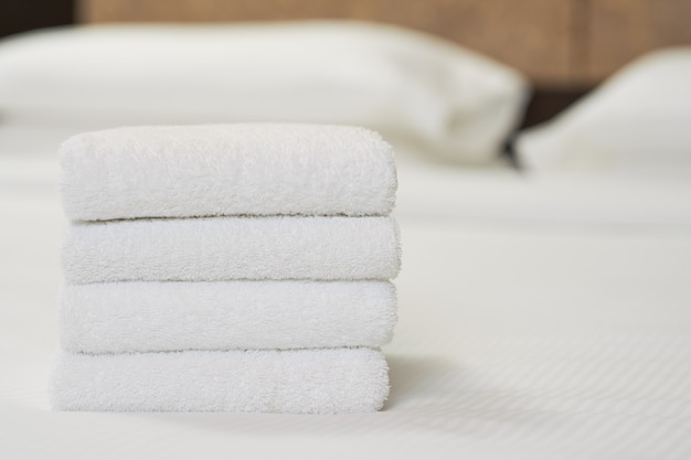 Gros plan de quatre serviettes blanches sur le lit dans la chambre d'hôtel pour le client. espace de copie. concept de service hôtelier